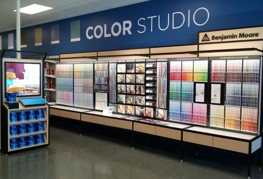 inside of paint store showing wall of paint samples with sign saying color studio above it